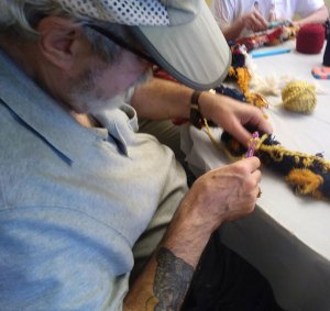A man with a tattoo and cap works on a group crocheting project.