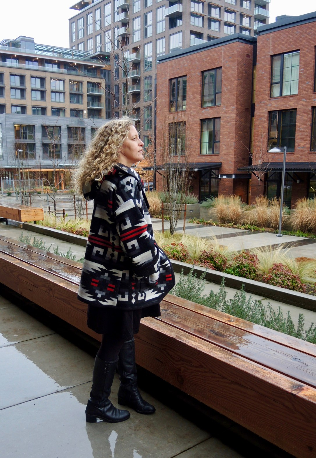A woman with blond curly hair stands in an urban setting wearing a coat made with Pendleton wool in Rio Rancho, a red and black pattern with white geometric shapes.