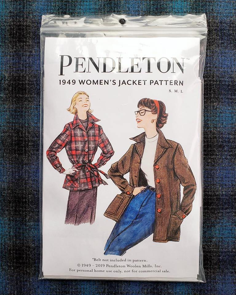 Photo of a jacket pattern for the Pendleton 1949 Jacket, sitting on blue and black plaid fabric. Pattern cover features drawings of two women in wool jackets.