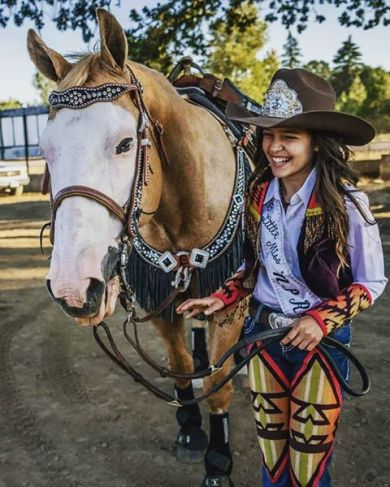 Young Western pageant princess wearing a cowboy hats and and riding outfit made with denim and Pendleton wool, her horse is with her..