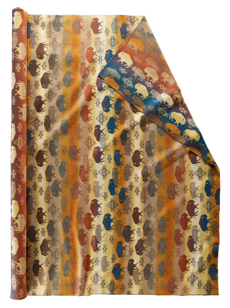 A roll of Pendleton wool fabric in Land of the Buffalo, featuring lines of buffalo or bison crossing the fabric horizontally in rust, red, brown, yellow and navy blue.