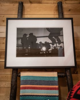 A framed black and white photo of cowboys sitting on a fence hanging on a ladder above a striped Pendleton blanket.