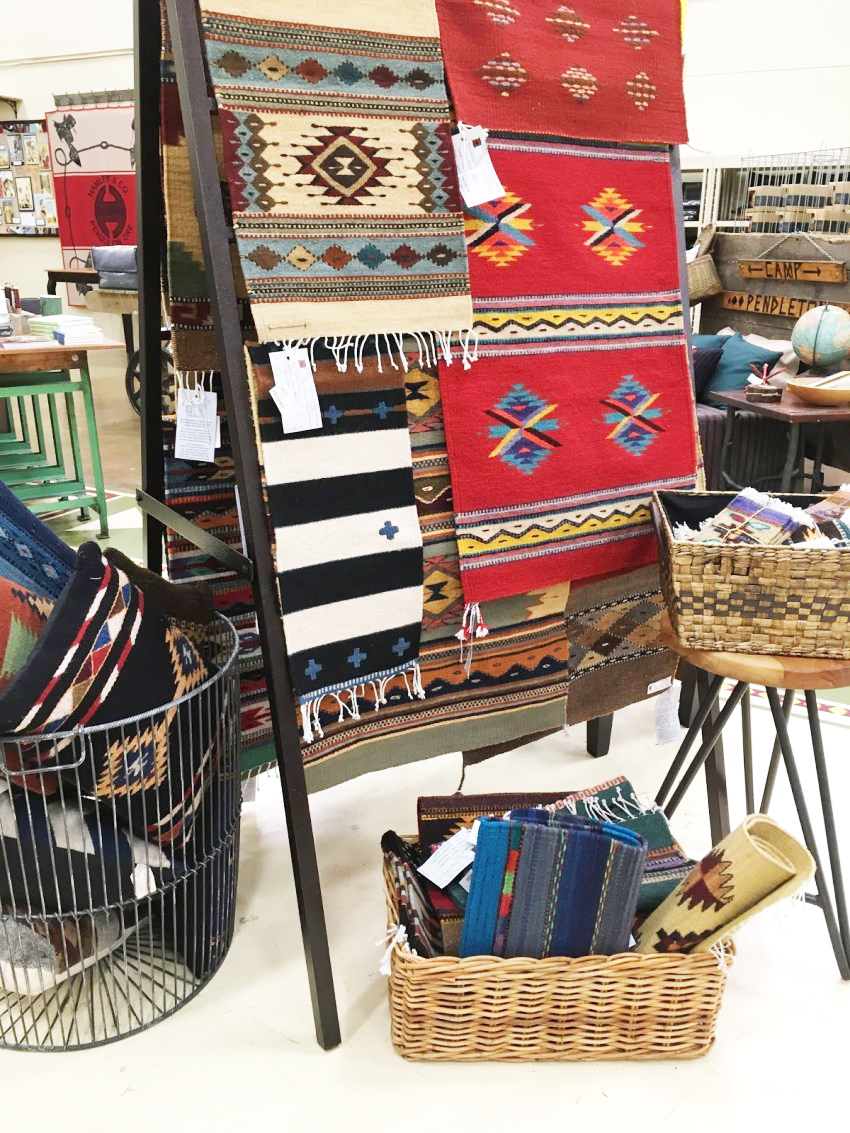 Store display of Escalante weavings on a ladder display rack, baskets of weavings on floor nearby.