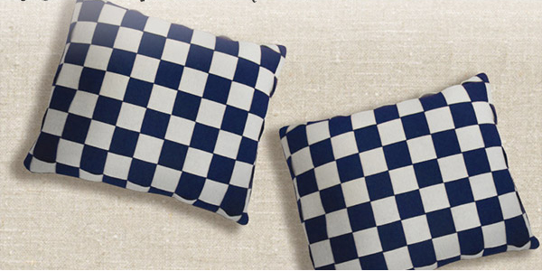 Two rectangular throw pillows made from weaving strips of navy and white wool lay on a background of of ivory fabric.