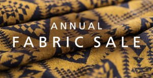 "A piece of gold and navy blue fabric in the Pendleton ""Basket maker"" pattern draped, with the words ""ANNUAL FABRIC SALE"" superimposed over the fabric."