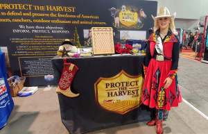 "Miss Rodeo Oregon, Taylor Ann Skramstad, posed by a booth for ""Protect the harvest."" She is wearing a red skirt, vest, and boots embellished with Pendleton wool."