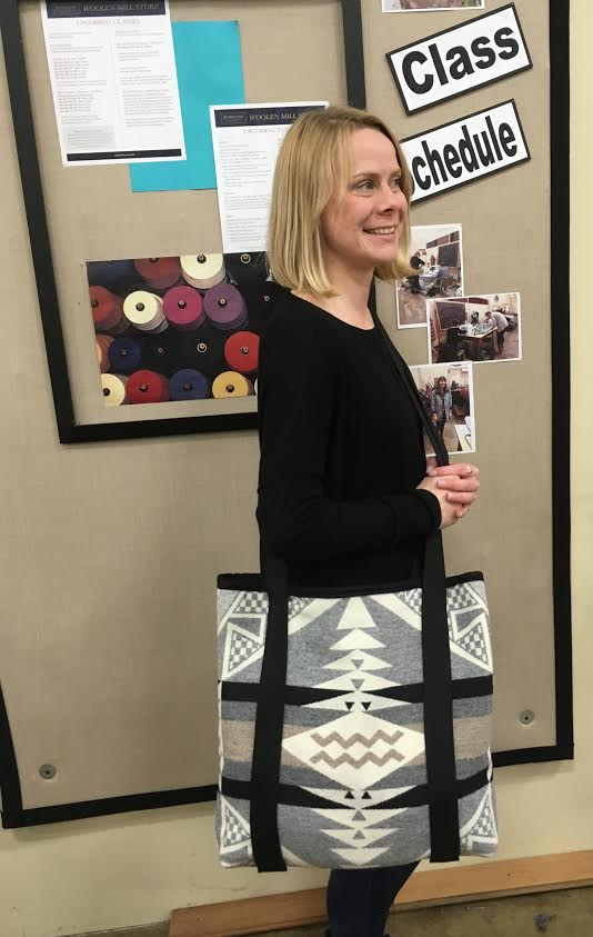 Jennifer stands in profile with the straps of a tote bag sewn from Pendleton wool over her shoulder.