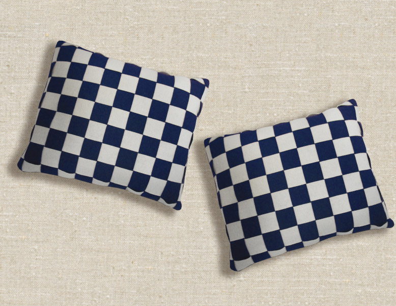 Two checkered pillows on a background of white linen. These pillows are made from strips of Pendleton wool felt binding in Navy Blue and White.