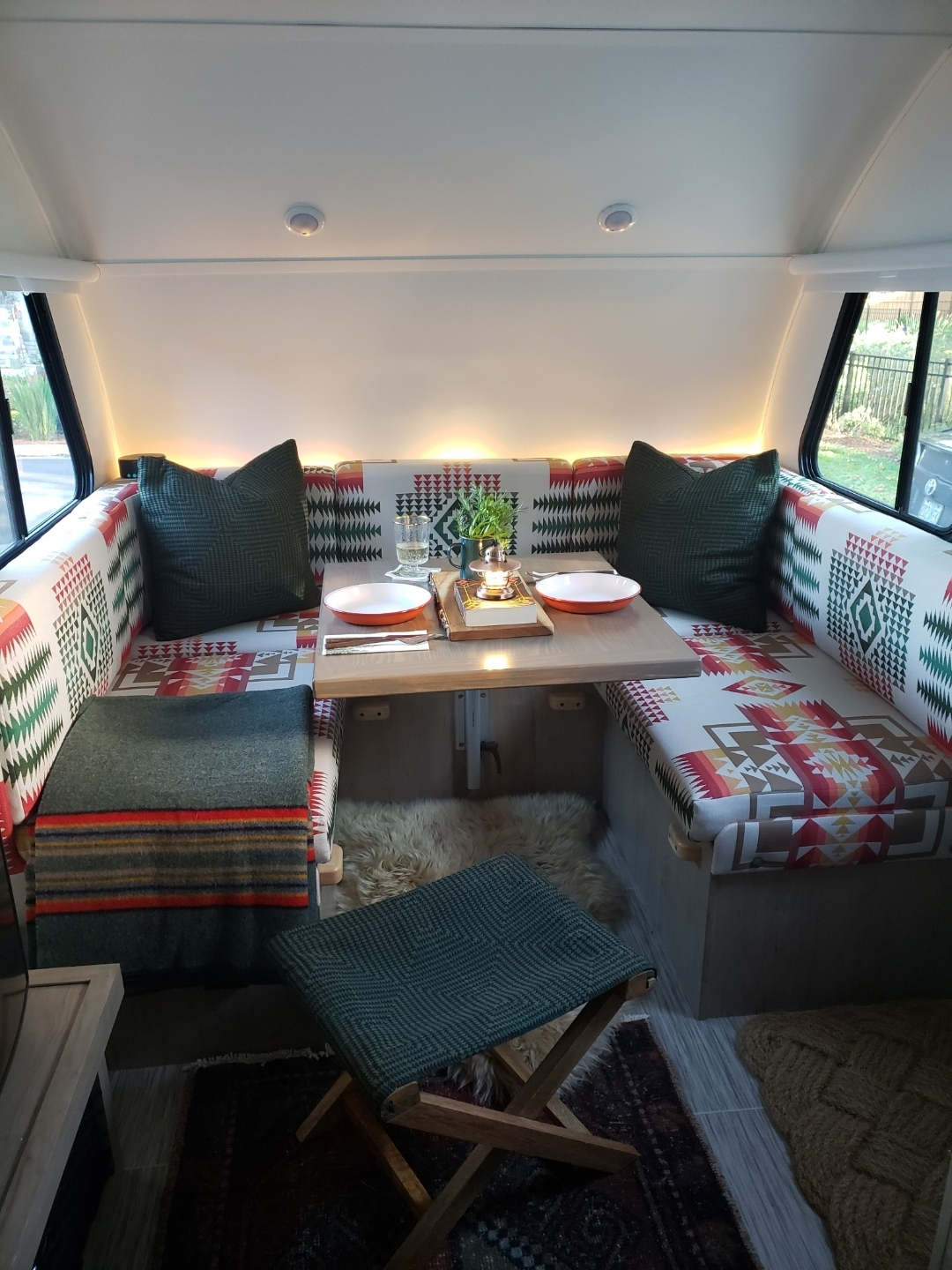 A U-shaped eating area in a camper with bright Pendleton by Sunbrella fabric cushions.