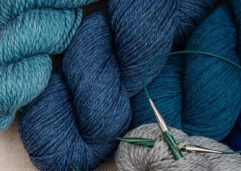 Skeins of blue yarns and knitting needles.
