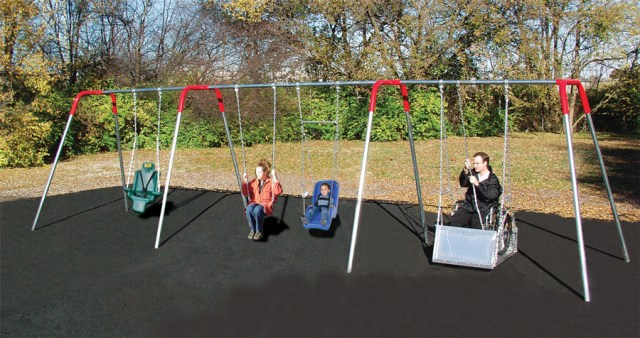 A swing set with a large fullback harness swing, a traditional seat swing, a smaller full harness swing, and a swing with a platform to accommodate wheelchairs