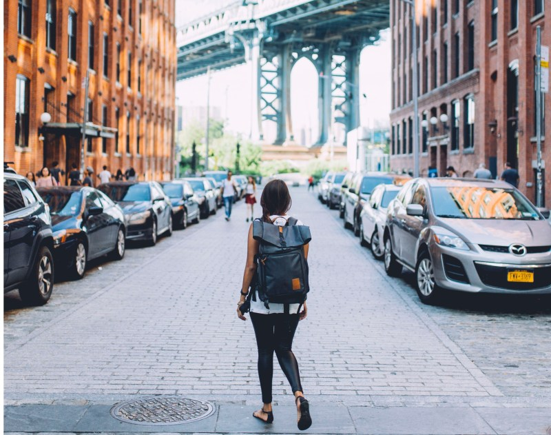 girl standing on crowded side street facing cars