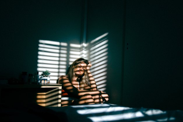what to read in August, girl in dark room looking tired