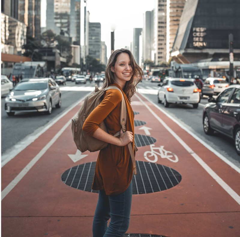 best travel products, girl standing in street with backpack