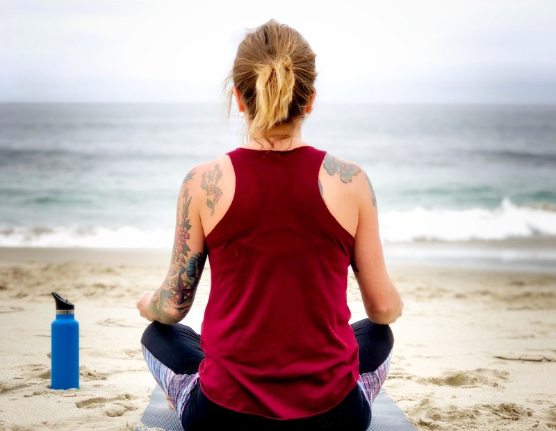 practicing mindfulness, girl doing yoga on the beach