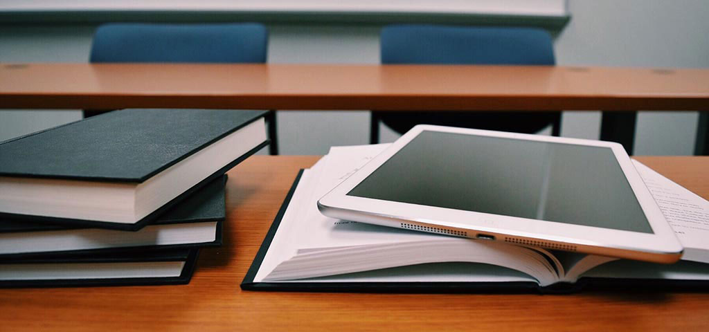 A tablet on top of an open book