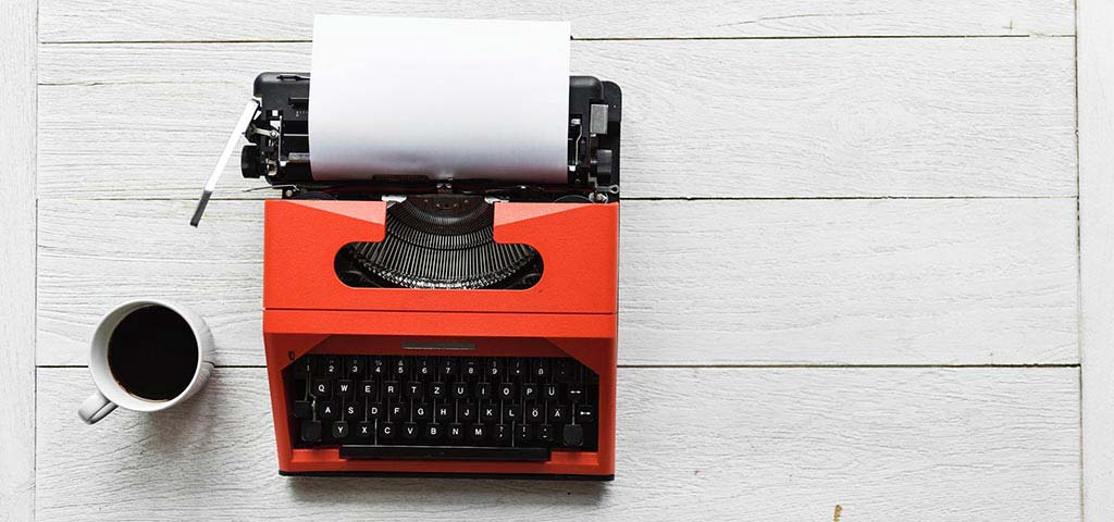 A red typewriter on a white wooden table
