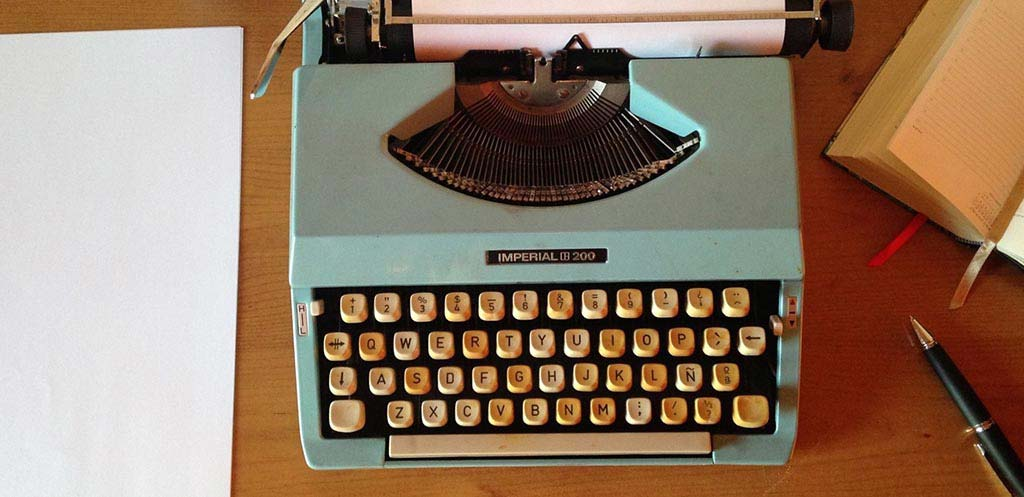 Teal typewriter on a wooden table