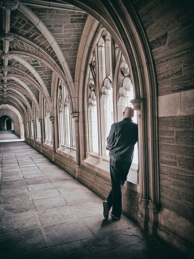 Man leaning against a cloisters wall