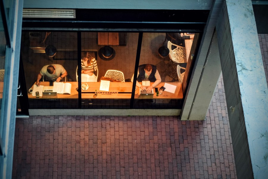 View of people working at a bench in a coffee shop, taken from above