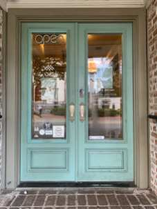 Bright blue doors adorned with COVID-19 regulation signs welcome customers at Mirabelle Cafe in Savannah Ga. on Tuesday, Sept. 29, 2020. This is done so that customers know the rules before entering the establishment. (J24/Isabella Cammisa)