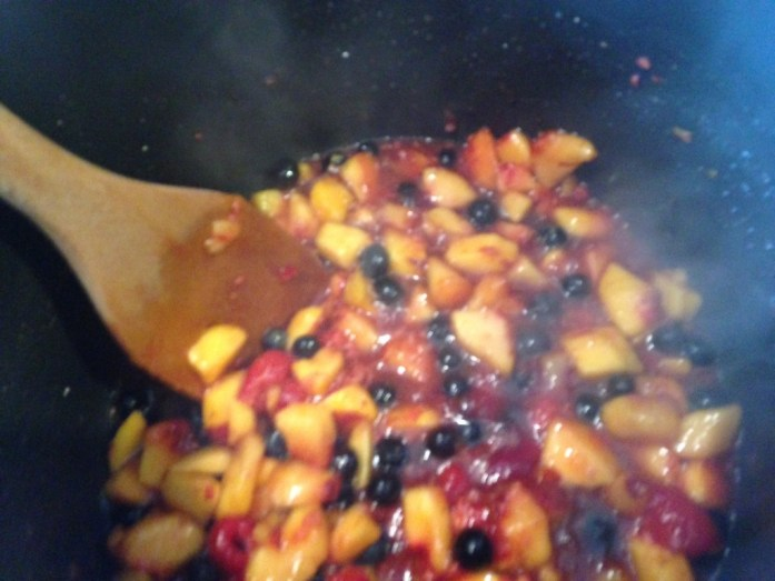 Steaming peaches, blueberries, and raspberries.