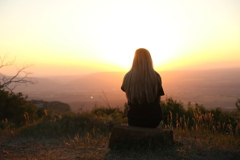 woman sitting on a mountain, sunrise