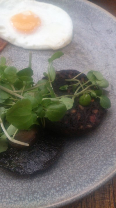Black pudding hiding beneath watercress