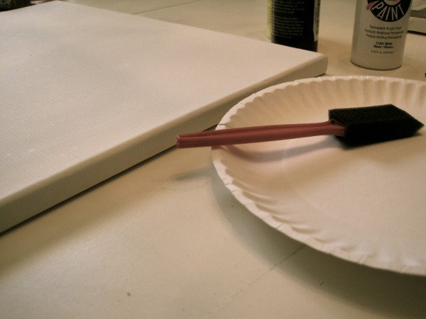 paper plate and paintbrush next to blank canvas
