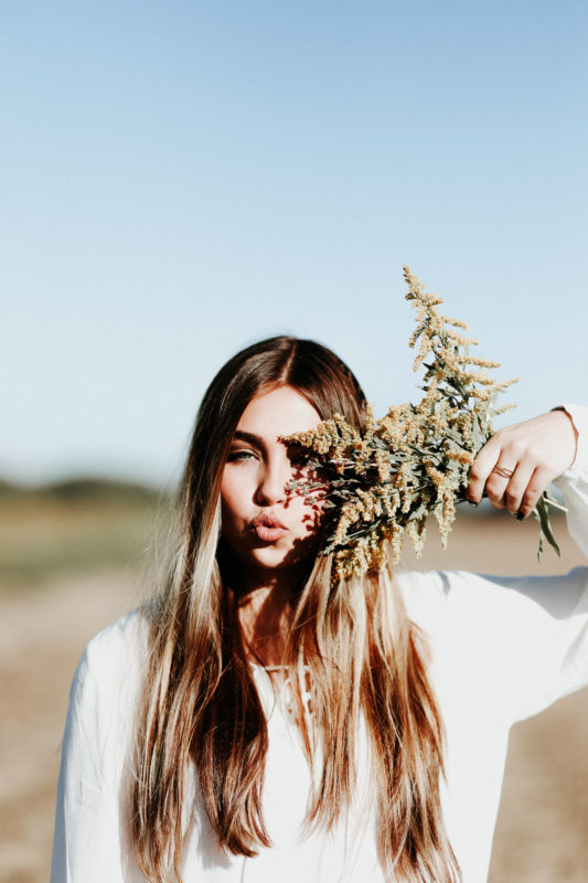 woman puckering up and hiding behind herbs