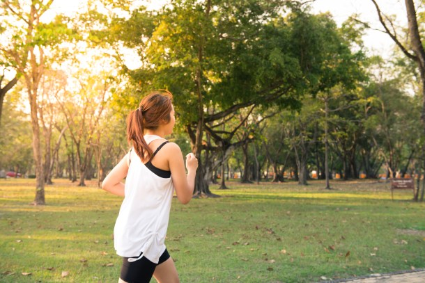 Young woman running in wood, training and exercising for trail run marathon endurance in morning sunrise. Fitness healthy lifestyle budget