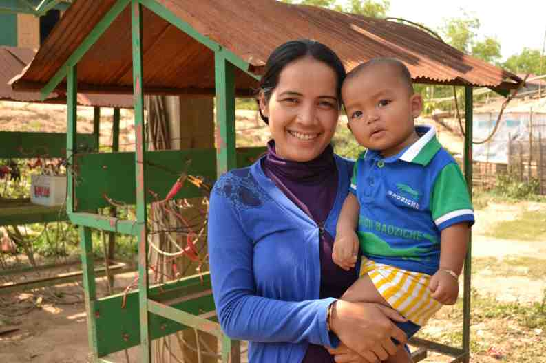 Tina & child in front of her micro business (solar battery charging station)