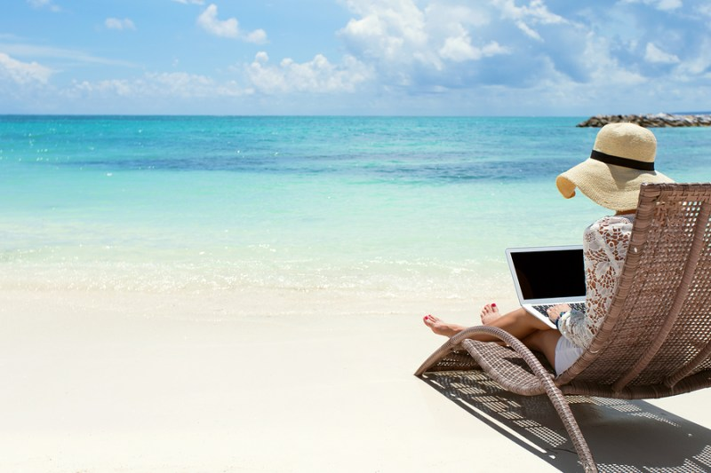 woman using laptop computer on the beach.