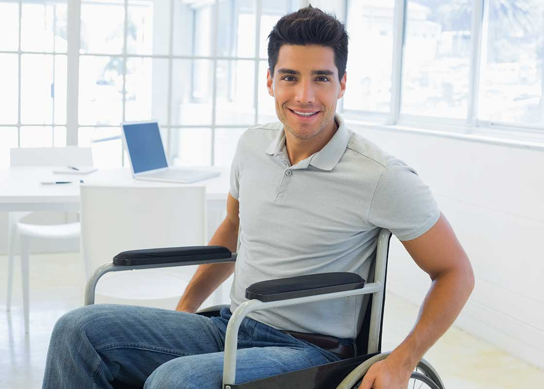 A man in a wheelchair smiles at the camera. His laptop is on a table behind him. | Un homme en fauteuil roulant sourit à la caméra. Son ordinateur portable est sur une table derrière lui.