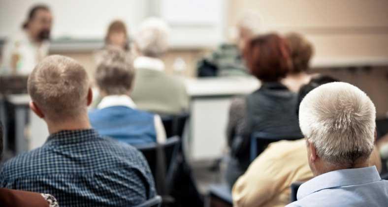 A group of men and women attending a seminar. | Un groupe d'hommes et de femmes assistant à un séminaire.