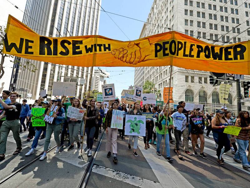 """Marchers carry a banner displaying the words """"We Rise With People Power"""""""