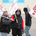 Masked strikers carry signs