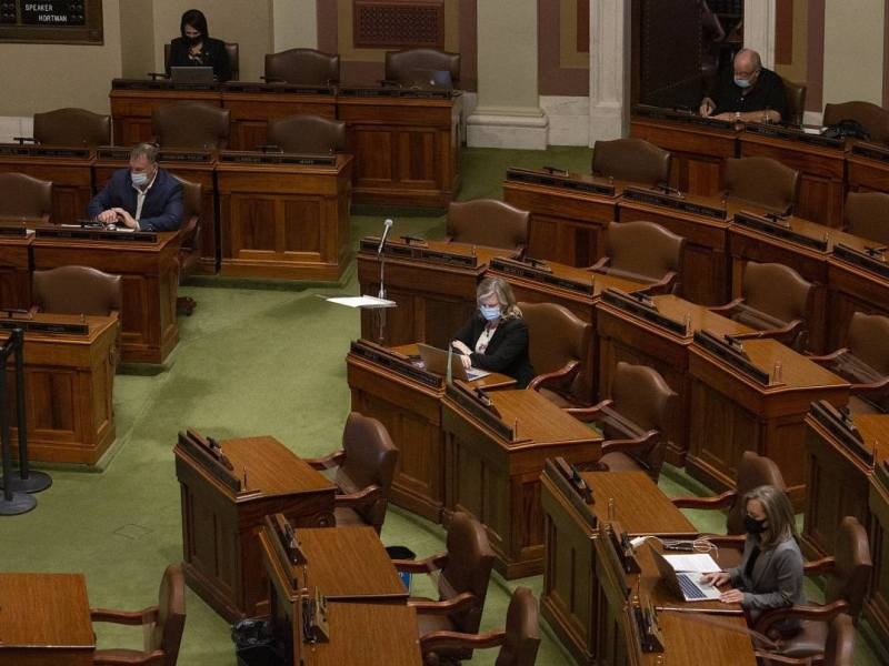 a few masked lawmakers sit socially distanced inside