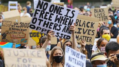 "picture shows large masked crowd at Black Lives Matter protest with most prominent sign reading ""No One is Free When Others are Oppressed"""