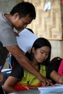 Loki, one of the college teachers, helps a student with her classwork.