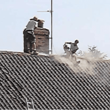 A roof cutter sitting on the top of a roof and cutting into tiles with clouds of dusts around him and no face or dust mask on
