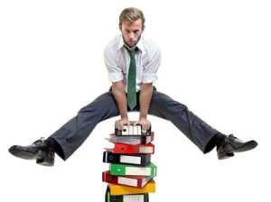A man leap frogging over a high pile of books and files in the workplace