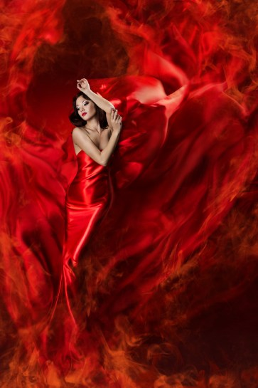 Beautiful woman in red waving silk dress as a fire flame. Lookin