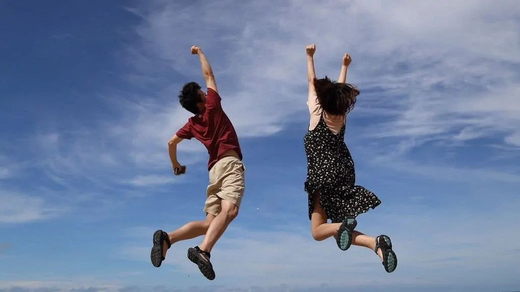 Two people jumping up tall and high