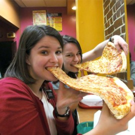 Two girls hogging in pizza