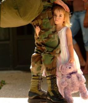 Child holding on to her father leaving for the army