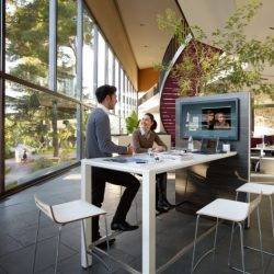 Colleagues talk in a bright and lively office design