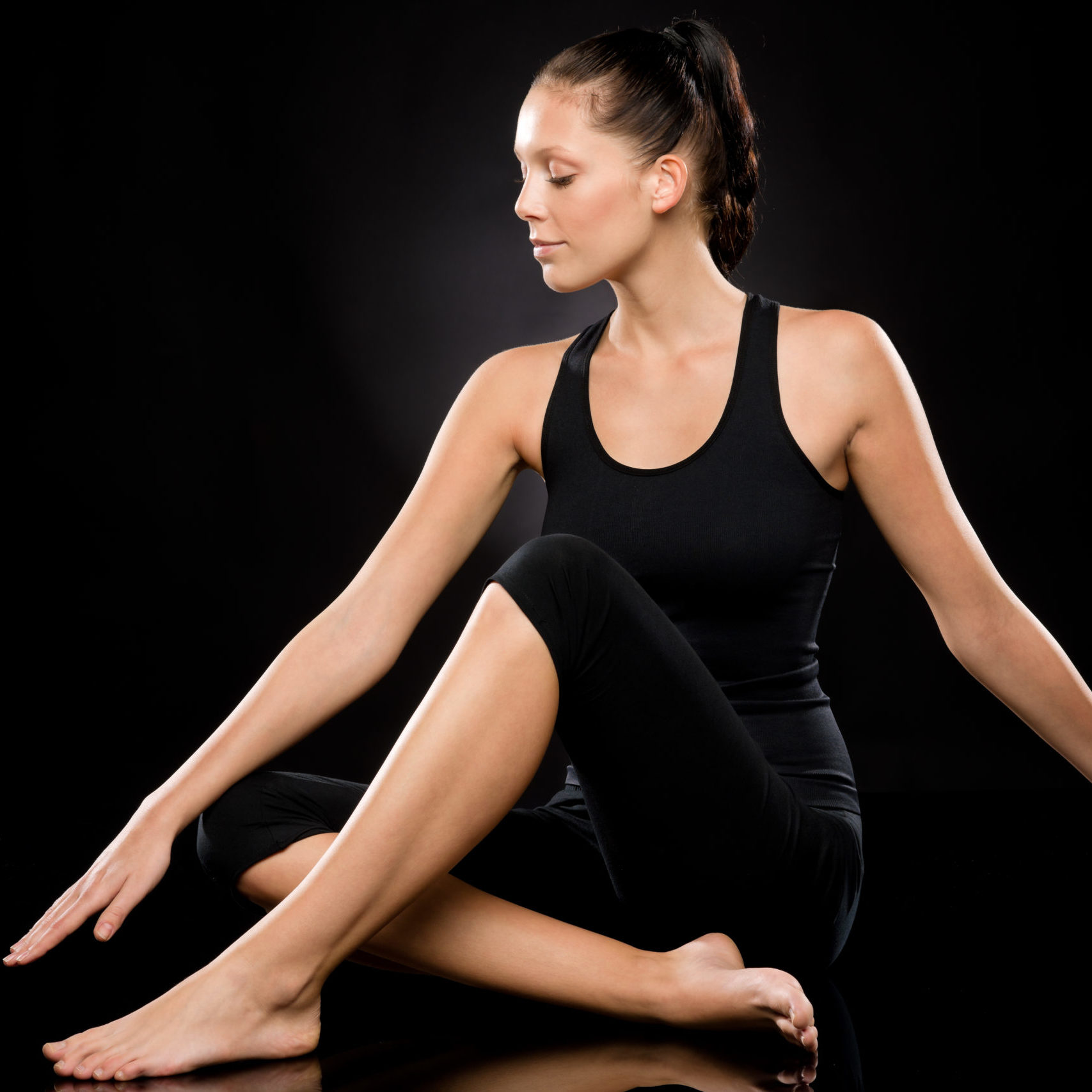 Tranquil young and barefoot woman performing yoga with stretched arms