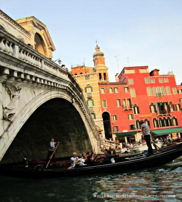 Sitting at the foot of the Rialto, watching gondolas pass.