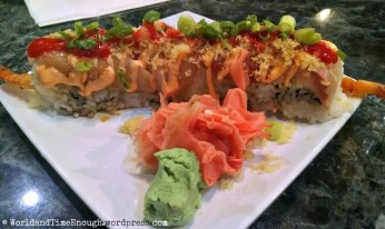 Trapper's STP roll: tempura shrimp, white onion & garlic cilantro sauce covered with avocado, topped with spicy yellowtail, tempura crumbs, hot sauce & warrior sauce.